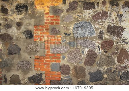Colored stone wall with red brick inset
