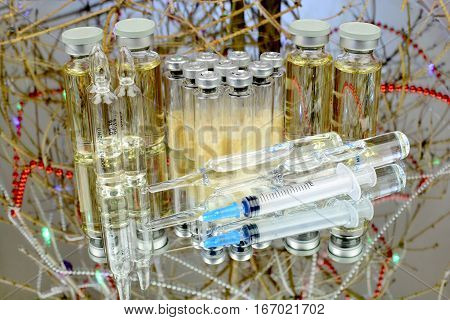 Vials of the vaccine against the background of the tree branches Medications for injection