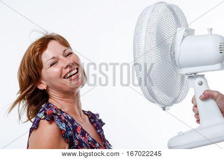 Brunette woman in studio smiles as a fan blows her air through her hair