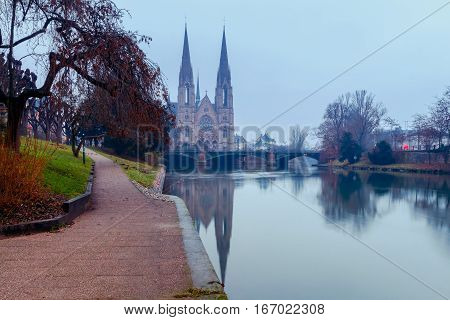 Picturesque views of the Reformation church with mirror images in Ile river at dawn. Strasbourg, Alsace, France.