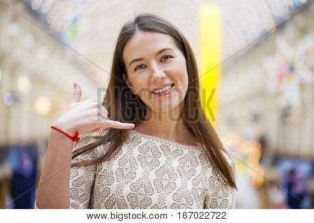 Sign Call Me. Young beautiful brunette woman in dress, posing against a background of shop interior