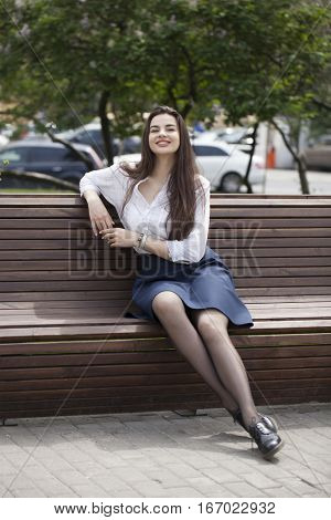 Young happy brunette woman in skirt and white blouse sitting on the bench in summer park outdoors