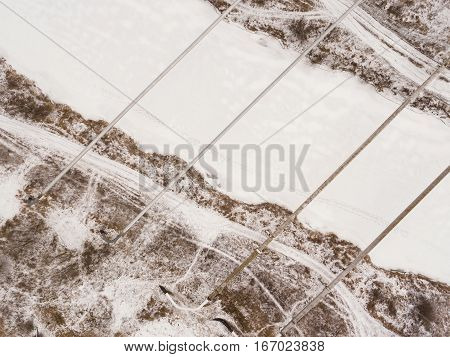 The pipes of the factory above frozen river. Steal big pipeline. Aerial view.