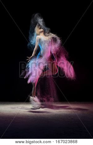 Slender girl jumping in cloud of pink and blue dust studio shot