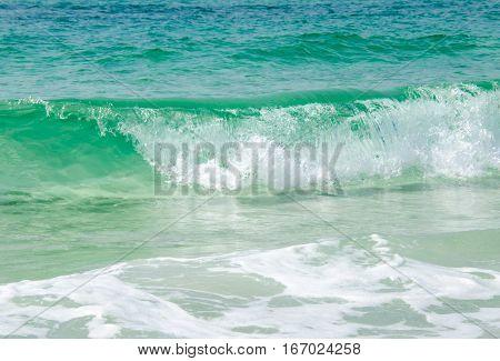 Warm tropical ocean beach waves splashing onto sea side shoreline.  Scenic travel destination location.  Blue green waters crashing ashore.