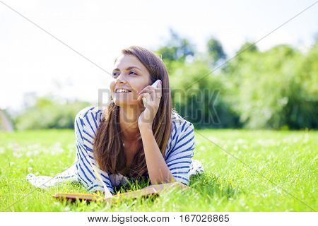 Young beautiful girl talking on a cell phone while lying on a green lawn in the summer park