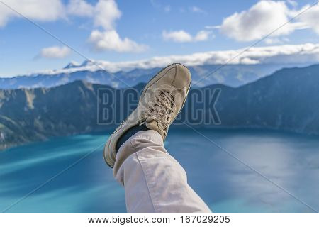 Funny photo showing a leg with trousers and shoes against quilotoa lake Latacunga Ecuador