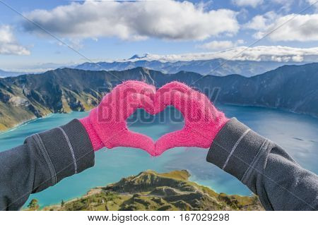 Hand with gloves forming a heart against spectacular biew of Quilotoa lake Latacunga Ecuador