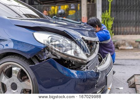 Car crash from car accident on the road in a city between saloon versus pickup wait insurance.