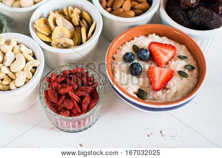 Healthy eating concept: paleo stye coconut porridge made with almond milk topped with strawberries various fruit and nuts on the back selective focus