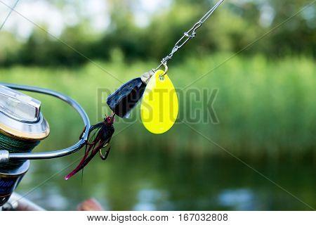 fishing spinning lure on fishing reel at the lake