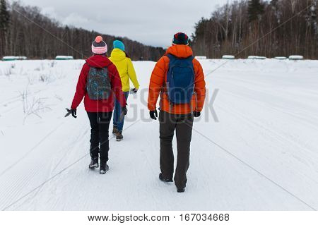 Young friends go in winter woods at afternoon