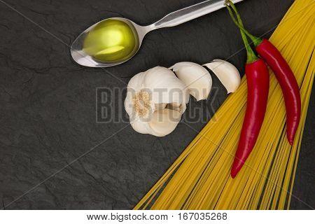 ingredients for spgaghetti aglio e olio on black slate: spaghetti, garlic, olive oil and red pepper