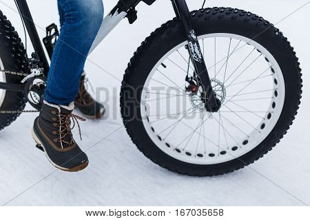 Photo of person with bicycle in winter forest in afternoon