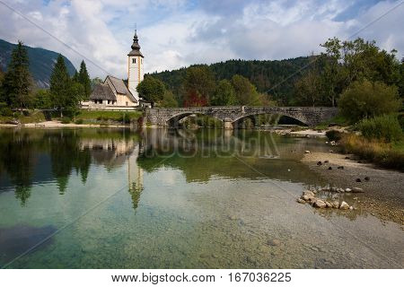 Bohinj lake landscape with calm water and reflection of St. John the Baptist church and the stone bridge in Ribcev Laz Slovenia at the start of autumn season.