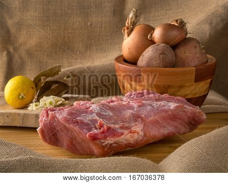 fresh pork loin over table with potatoes garlic and lemon