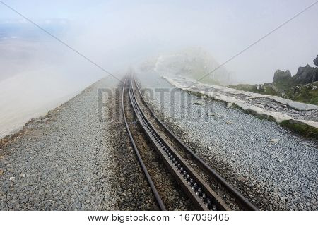 Railway in Snowdonia National Park, North Wales, United Kingdom in a foggy autum day, selective focus