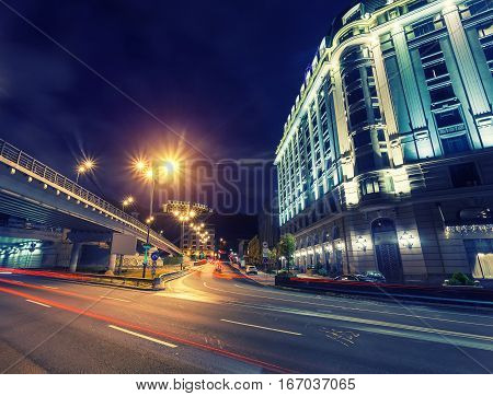 Car light trails and urban landscape. Moving car with blur light through city at night. Kiev city, Ukraine.
