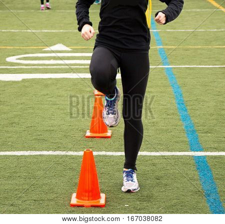A runner is performing a running drill over orange cones