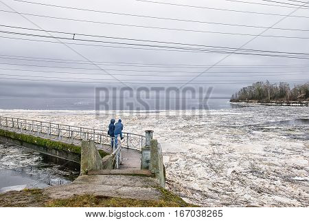 Ivangorod. Russia. Narva Reservoir. People standing on the icebreaking wall, and the pedestrian bridge on the wall opposite Estonia. Reservoir is located on the Russian-Estonian border