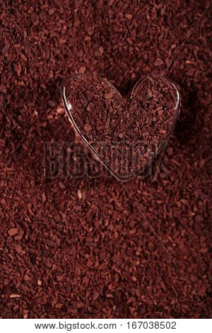 heart shaped glass with grated dark chocolate, perfect color and background