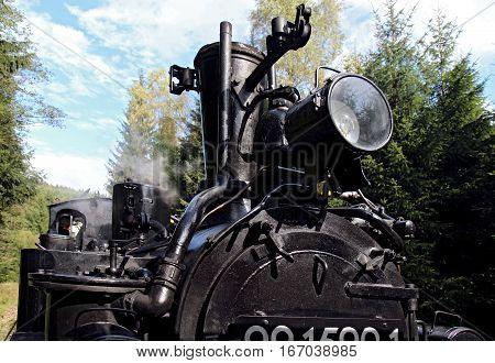 detail of black old steam locomotive in action