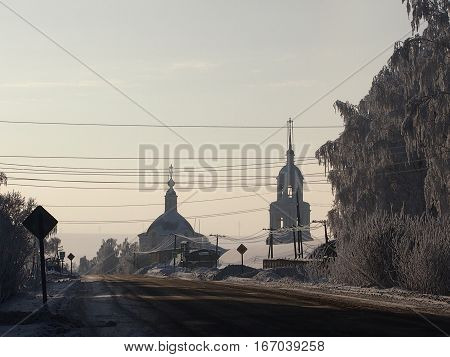 Roadside orthodox church with a belltower against the background of the winter sky