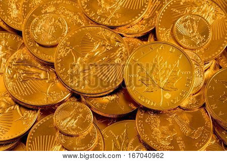 Canada Maple Leaf one ounce gold coin against a golden background of other coins with focus on the leaf