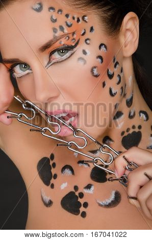 beautiful woman with animal patterns and collar on dark background