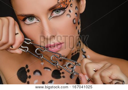 young woman with an animal face art and spines on dark background