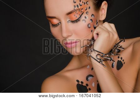 beautiful woman with animal face art and spines on dark background