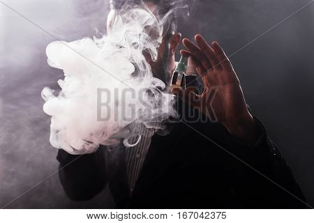 A Man In A Hood Holding Liquid And Exhales Vapor
