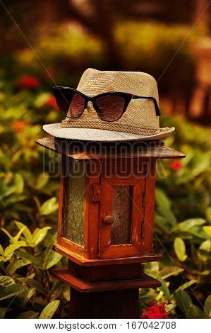 The stylish hat, muff, napper with sunglasses, spectacles is standing on the lamp with warm tones in summer time