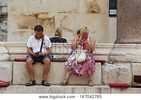 SPLIT, CROATIA - SEPTEMBER 11, 2016: This is step of the peristyle of Diocletian's palace in which unidentified tourists relax over a cup of coffee and transmit urgent messages online.