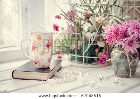 Cup of coffee or tea with a book and pink flowers on a white table near the window. Cozy autumn or winter breakfast. Provence style. Lifestyle morning background.
