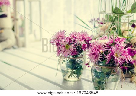 Provence style interior - beautiful pink and purple bouquets in glass vases over window. Light home decoration with flowers asters. Retro living room. Vintage holiday floral concept. Copy space.