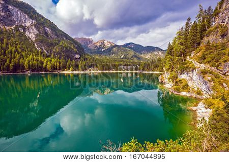 The emerald smooth surface of water reflects wood and mountains in coast of the lake. The concept of walking and eco-tourism. Magnificent lake Lago di Braies, South Tyrol