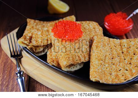 pancakes with red caviar and lemon in a cast iron skillet