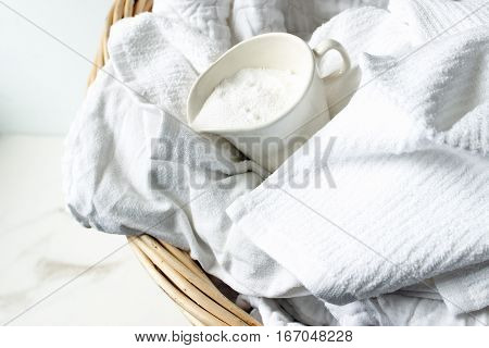 Bright, white clean laundry in wicker laundry basket with detergent.
