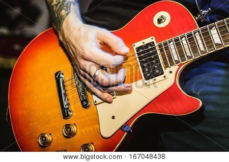 Musician. Blurred hands on guitar string guitar closeup. Live rock music concert.