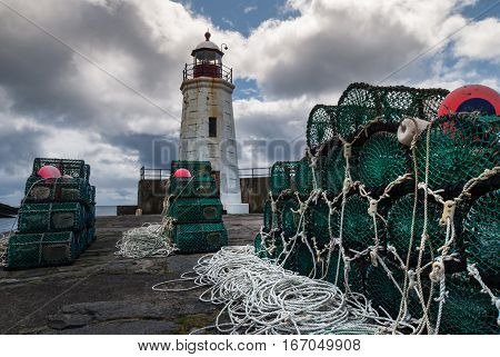 Lybster Scotland - June 4 2012: Green lobster traps are stacked on black stone pier of Lybster harbor with white lighthouse in back. White cords and red buoys. Dark clouds in blue sky.