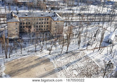 The aerial View of urban fringes in Kyiv, Ukraine in sunny winter day.View over the city rooftops with sunlight and snow at Kiev Darnitsa suburb.Heating and Power Plant, moderns buildings, school, uptown