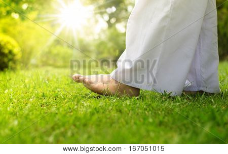Woman buddhist walking on green grass for relaxation and meditation over sunlight