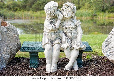 statue of children on green bench in garden with pond