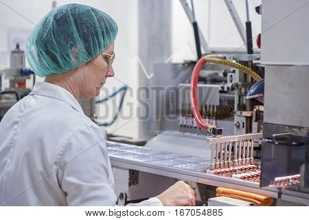 Pharmaceutical Production Line Worker at Work. Robotic arm lifting ampules at packaging line in pharmaceutical factory.