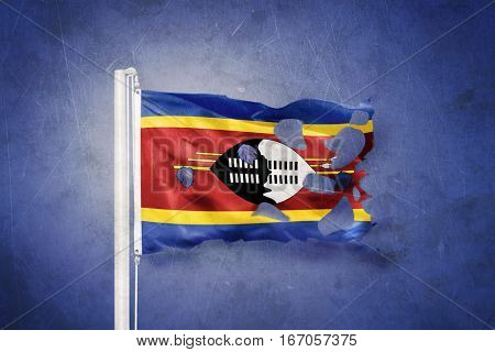 Torn flag of Swaziland flying against grunge background