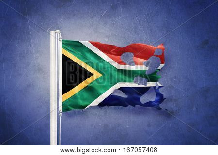 Torn flag of South Africa flying against grunge background
