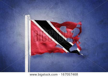 Torn flag of Trinidad and Tobago flying against grunge background