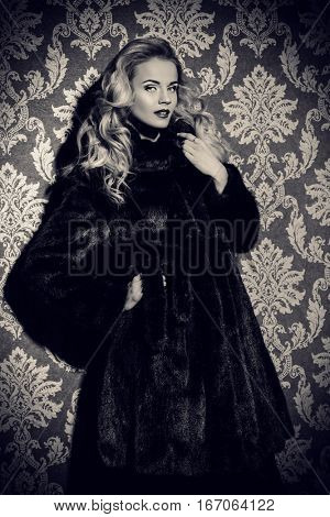 Beautiful blonde woman wearing mink fur coat. Fashion, beauty. Luxurious lifestyle. Studio shot over vintage background.