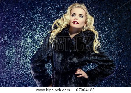Fashion shot of a beautiful blonde woman wearing mink fur coat. Luxurious lifestyle. Studio shot over black background.